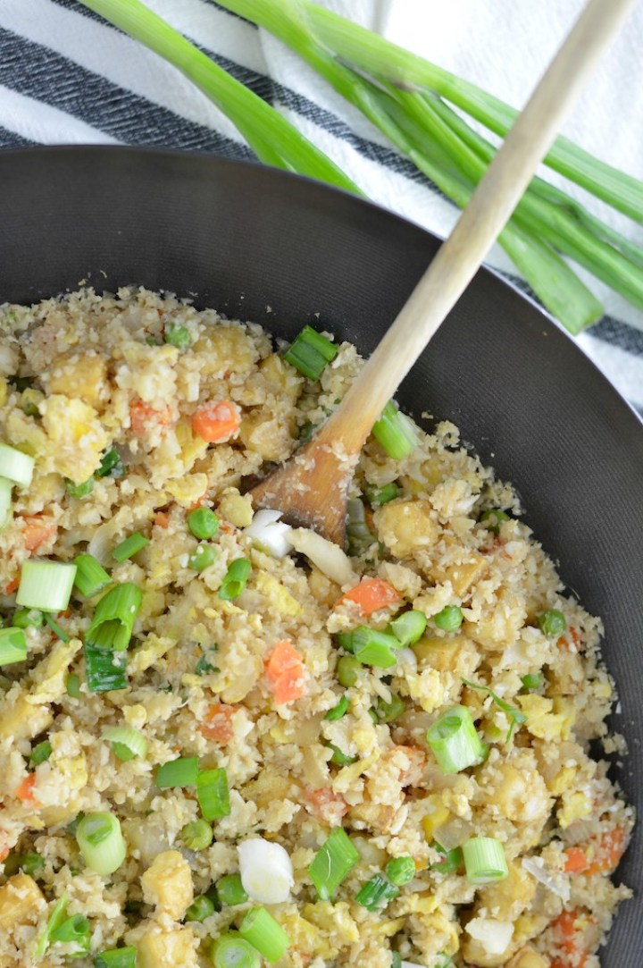 close-up overhead shot of cauliflower fried rice in wok with wooden spoon