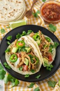 shredded chicken tacos on black pate