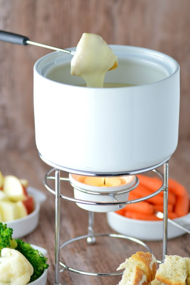 close-up of classic cheese fondue with bread dipping in cheese
