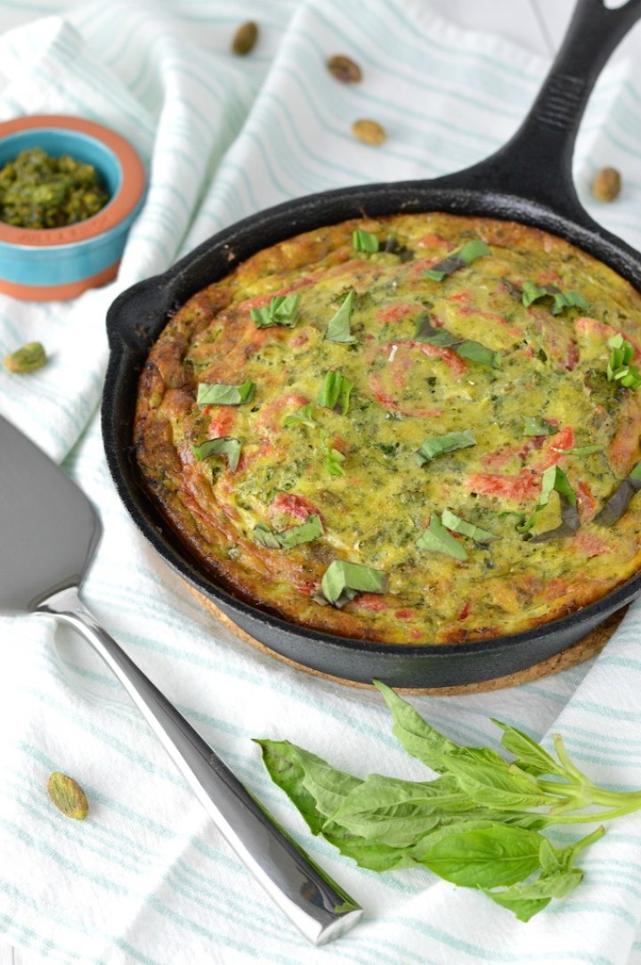 Italian frittata in cast iron skillet with fresh basil and pistachios