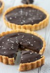 close-up of chocolate caramel tart with one slice cut