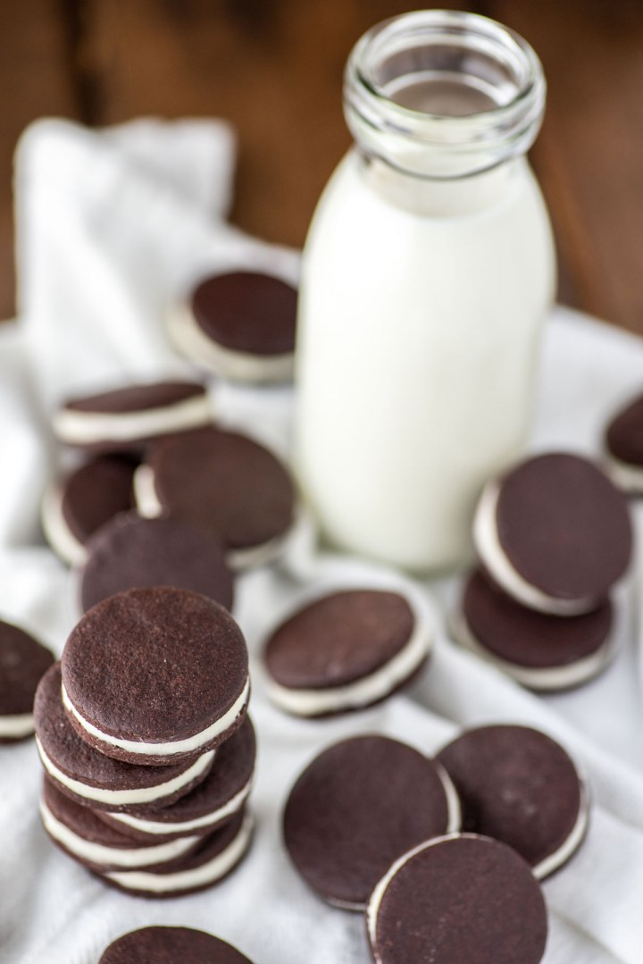 close-up of stacked homemade oreos on white kitchen towel with glass of milk