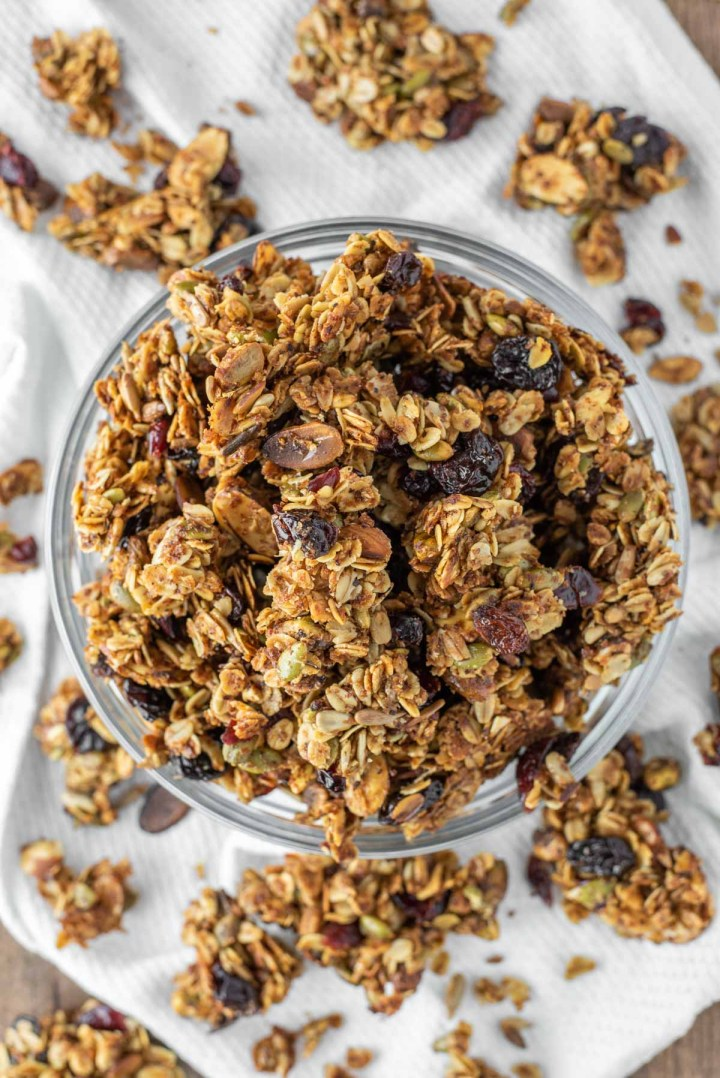 overhead shot of fruit and nut granola in glass bowl