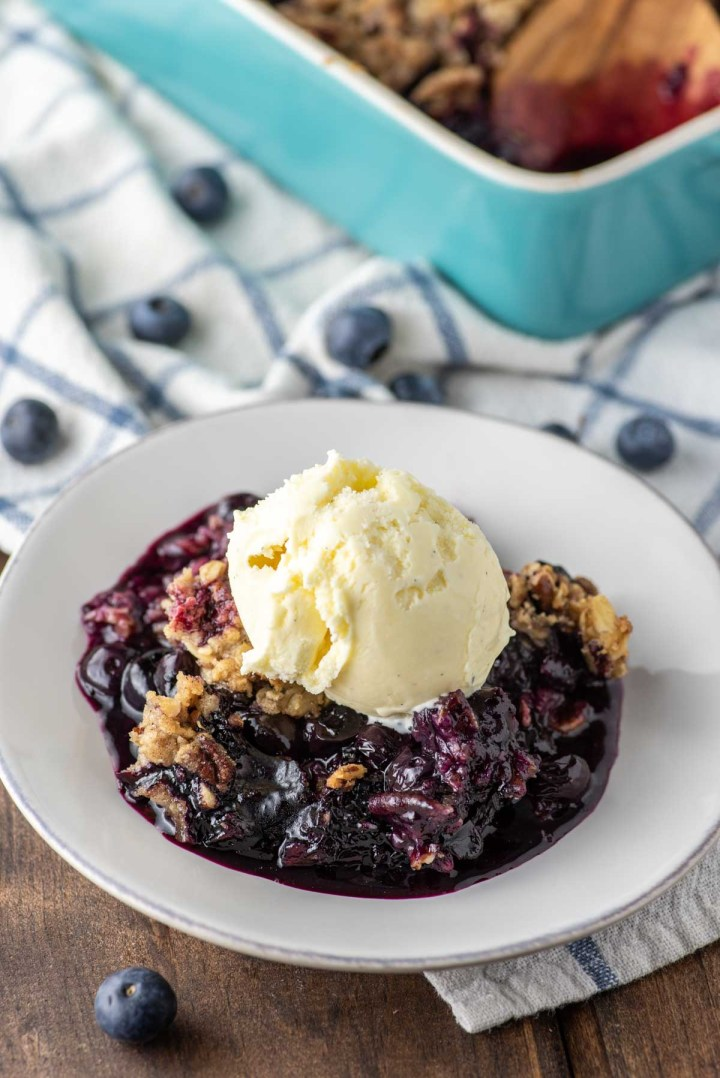 blueberry crisp on plate topped with ice cream