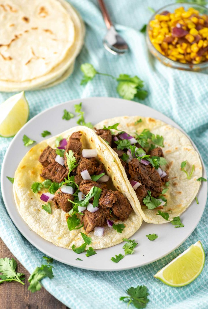 two carne asada tacos on plate on dish towel