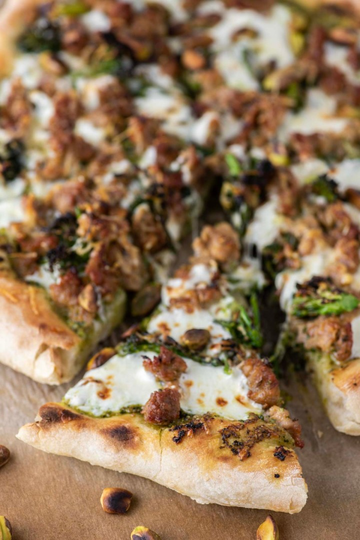 slice of broccoli rabe pizza being pulled away on parchment paper
