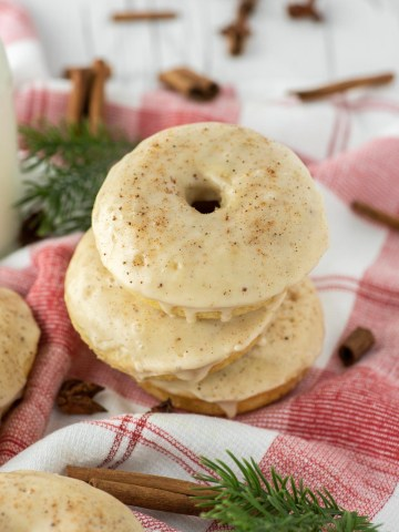 three eggnog donuts stacked on dish towel