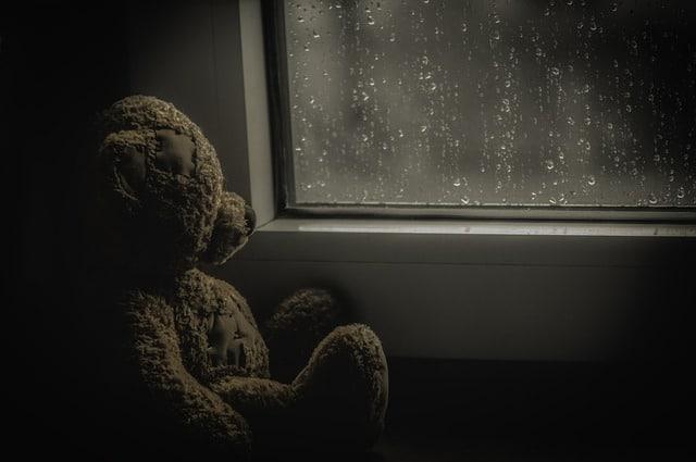 暗い部屋の中から外を眺めるテディベア