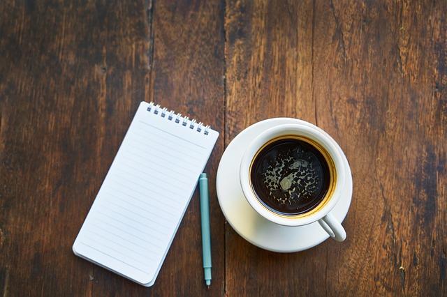 テーブルの上に置かれたメモ帳とペンとコーヒー