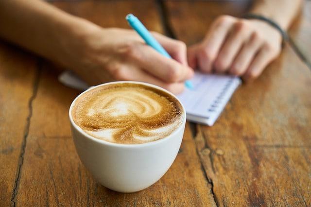 コーヒーとメモ帳に水色のペンでメモしている男性の手