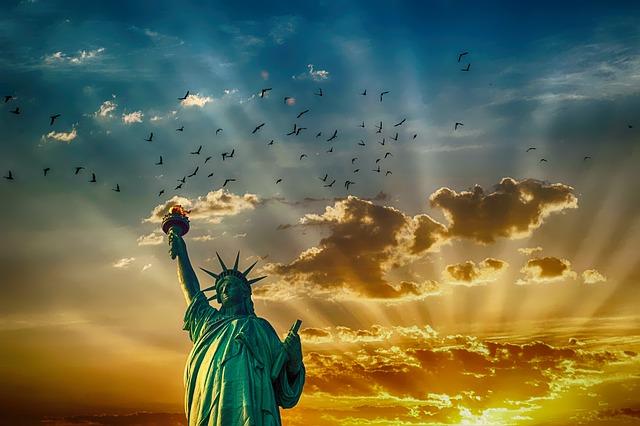 朝日に照らされた自由の女神と空をはばたくたくさんの鳥の群れ