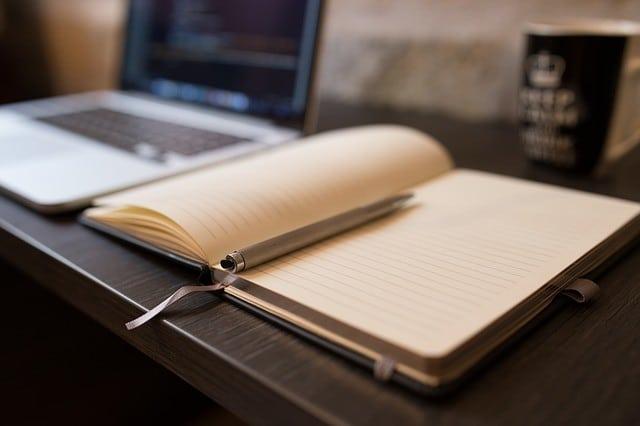 本の間に置かれたペンその横にあるパソコンとコーヒー