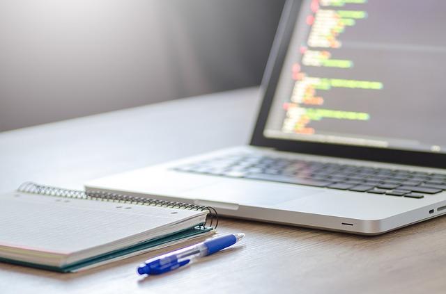 デスクの上に置かれたプログラムのコードが表示されたパソコンとメモ帳とペン
