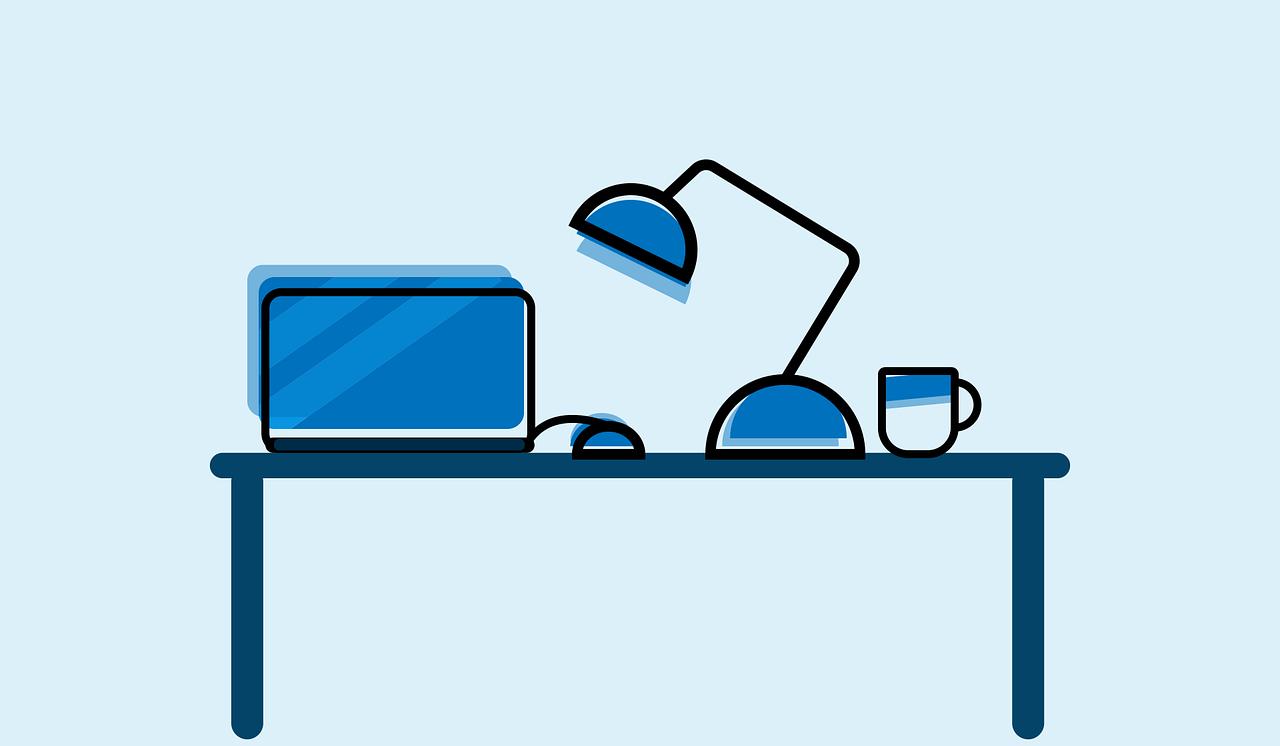 デスクの上にあるパソコンとマウスとマグカップとスタンド