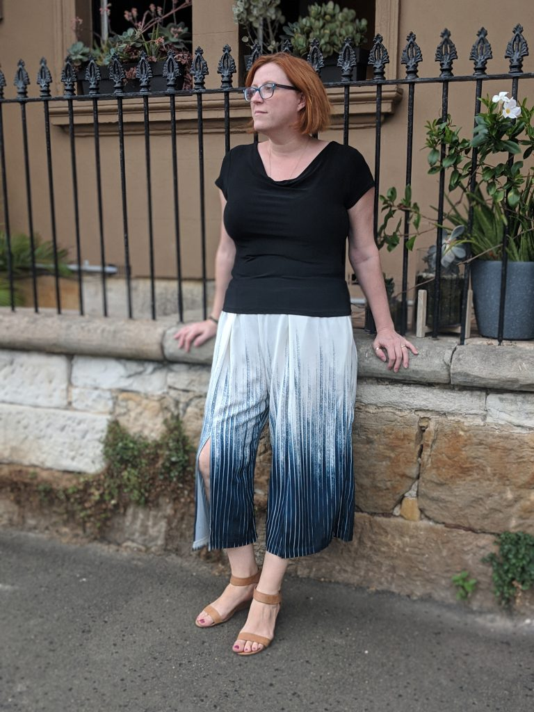 The author leaning against a wall and railings wearing a black top and drapey cropped pants with a blue striped ombre pattern.