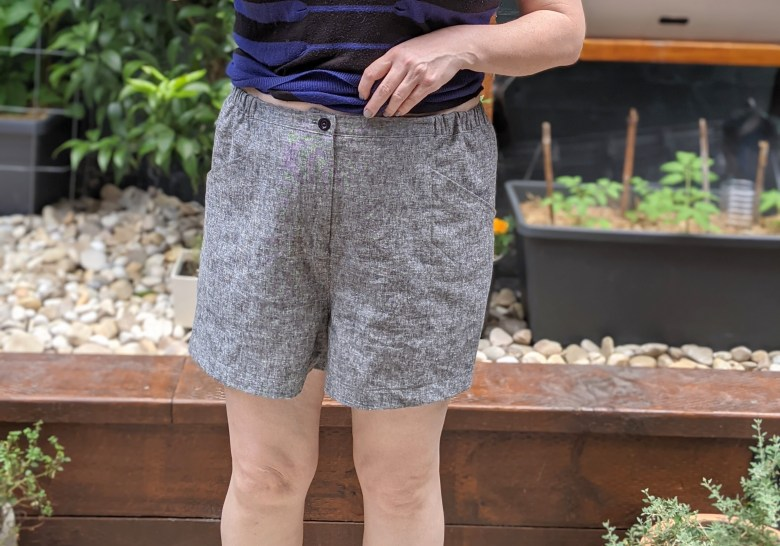 Close up of the grey shorts from the front - you can see the elastic sides and the front fly and button.