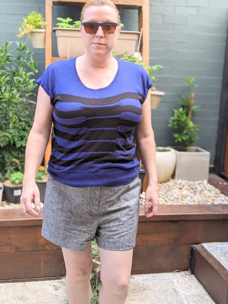 The author standing in her backyard front on to the camera.  She is wearing grey shorts, a blue and black striped top and sunglasses.