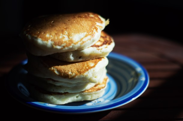 A dark moody photo of large, fluffy, pancakes on a dark blue plate.