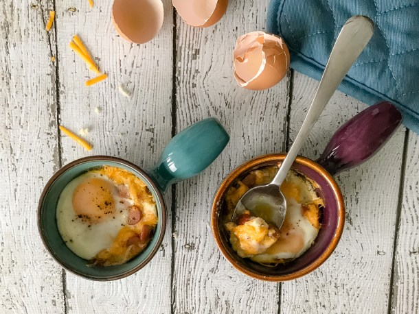 An overhead shot of Cheesy Oeufs en Cocotte with broken eggshells and an over mitt visible next to the pots that the eggs were baked in.