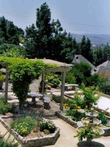Mediterranean garden with pergola and fountain and raised vegetable beds