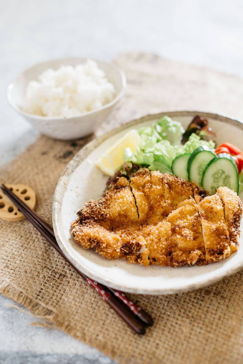 a bowl of rice, a plate of chicken katsu and green salad on an oval plate.