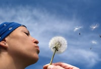 Letting go and feeling peacful - woman blowing dandelion