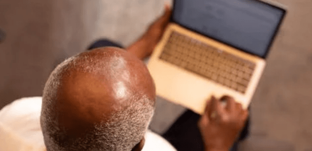 bald man using a laptop