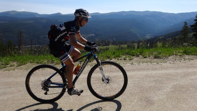 Bryan Alders climbing up through Winter Park ski area on the way to preride the XC course