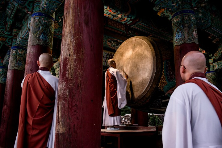 Buddhist monks watching a drum ceremony