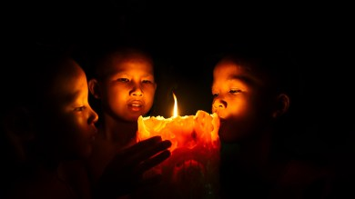 Young monks gather around a candle at Angkor Wat, Cambodia