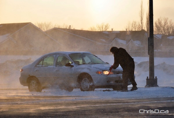A motorist clears their car off during the morning commute on Friday, February 18, 2011. (MARC EVANS / CHRISD.CA)