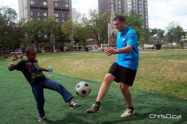 A Cadet with the Winnipeg Police Service plays soccer with a boy in Central Park in this file photo. (HANDOUT)