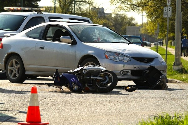 A scooter sits on its side near where a driver was thrown off after being involved in a crash with a car on Thursday, May 3, 2012. (HOWARD WONG PHOTO)