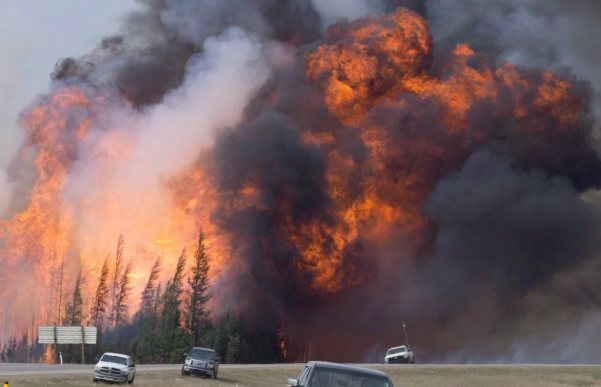 A giant fireball is visible as a wildfire rips through the forest by Highway 63, 16 kilometres south of Fort McMurray, Alta on Saturday, May 7, 2016. (THE CANADIAN PRESS/Jonathan Hayward)