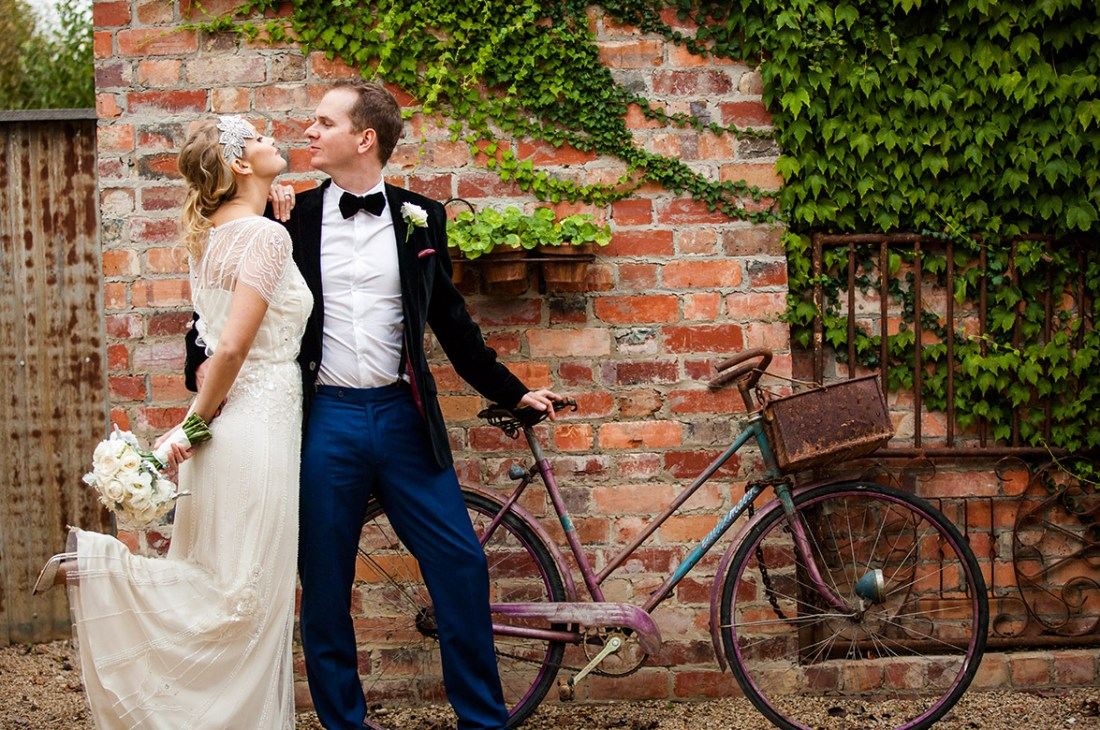 Melbourne Wedding Photographer at Stones of the Yarra Valley with bride and groom standing next to a vintage bike