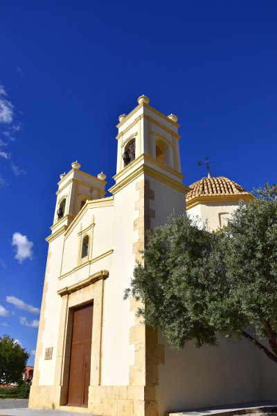 kapel in la Nucia, zonnige dag met blauwe lucht en groen boom naast de kapel, in oude kern La Nucia