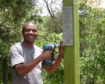 Sheunesu attaching the plaque Declaring God's Glory over Zimbabwe