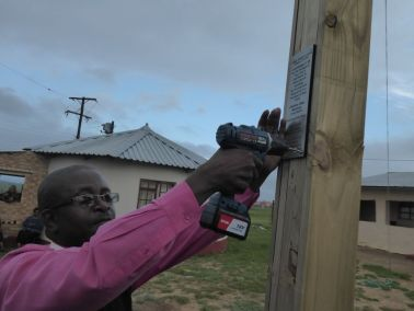 "Pastor Matya attaching plaque ""Giving God Glory"""