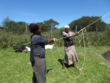 Ladies stabilize the Cross by holding the ropes tightly