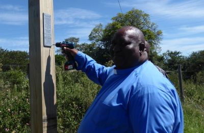 """Pastor Malindi attaches the plaque """"Giving God Glory"""" over Colombo, South Africa and entire ministry area"""