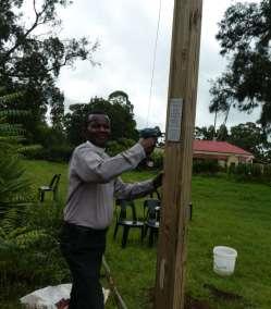 Reverend C P attaching plaque Declaring God's Glory