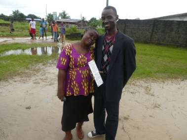 Pastor & Wife hold plaque Declaring God's Glory over Liberia as rain stops