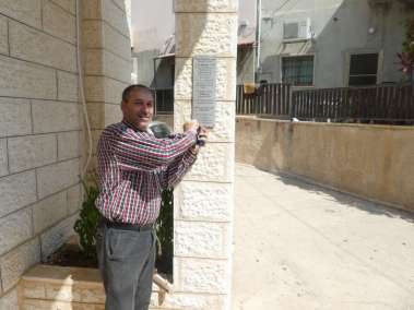 Pastor Khoury attaches plaque to church column
