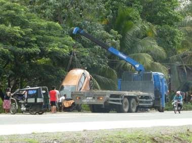 Truck crane retrieving car after hitting tree