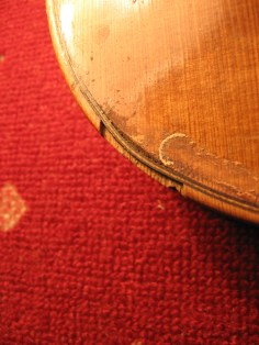 Schadhafter Deckenrand einer Geige/ damadged edge of a violin at chin rest position