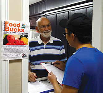 Volunteers at Highland Park Christian Church such as Jack Foreman (left) welcome and visit with every client who enters. The church primarily helps folks who have food needs.