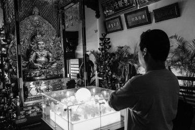 Man praying in the Buddha Tooth Relic Temple, Singapore