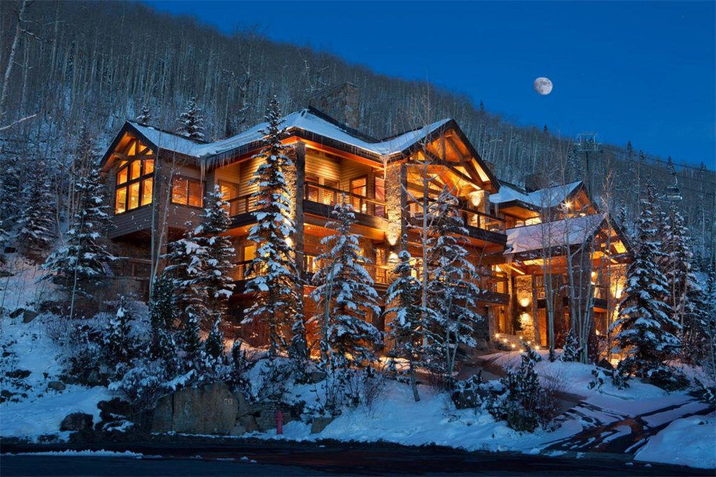 """<b>US$7,250,000<br/>5 Bedrooms, 8,861 sq. ft.</b><br/>Anchored on a lushly wooded hillside overlooking the Mountain Village """"core,"""" with on-grade ski access from the lower level, this exquisite residence is convenient to village center amenities and the gondola. A bold façade of stone and timber with a European flair blends perfectly with its setting. The impeccable interiors are adorned with cherrywood finishes, flagstone floors, and granite and travertine bathrooms. The stellar amenities include two master suites, a theater room, family room with wet bar and fireplace, chef's kitchen, and ski room opening to the trail."""