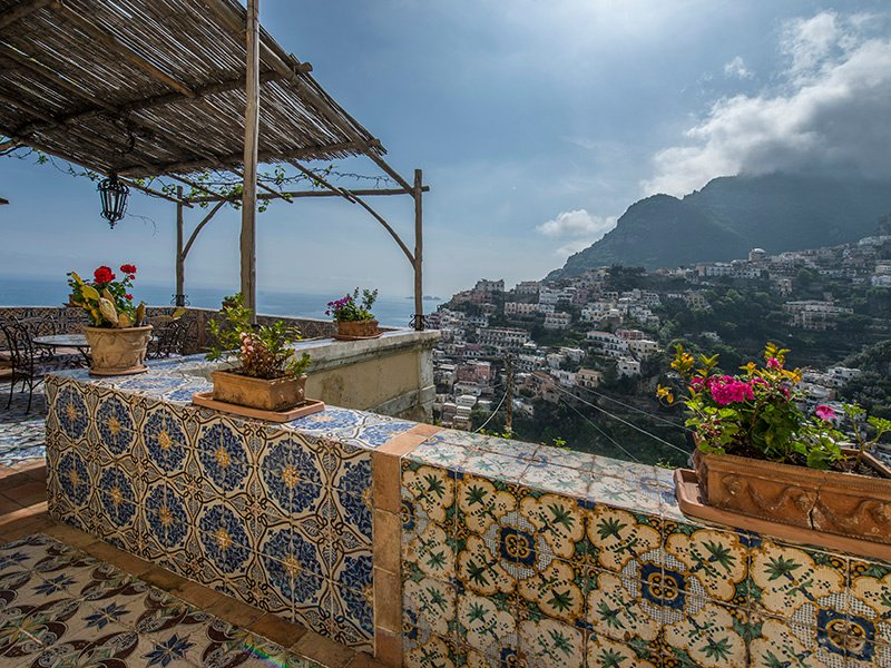 Set in a historic Positano building, this Neapolitan Baroque-style apartment boasts high frescoed ceilings and colorful majolica decor.