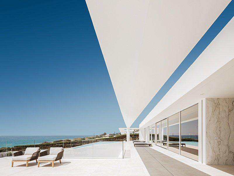 A área da piscina do Villa Escarpa é um oásis de branco com vista para o litoral da Luz em Portugal.